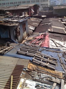 The hodge-podge of tin, wood pallets, tarpaulins, and other building materials that make up the roof of this old complex.
