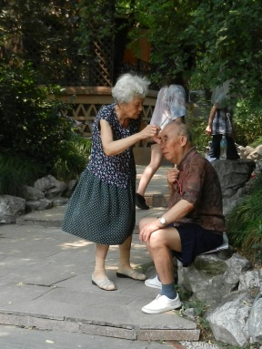 A woman gives her husband a haircut in the park in Shanghai